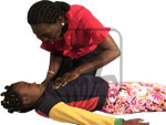 Woman practicing approach on what to do for a child cardiac emergency.